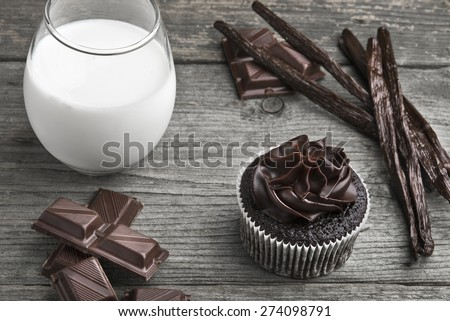Chocolate cupcake with dark chocolate icing, vanilla beans, chocolate and a glass of milk on a wooden background\r\r\r\r