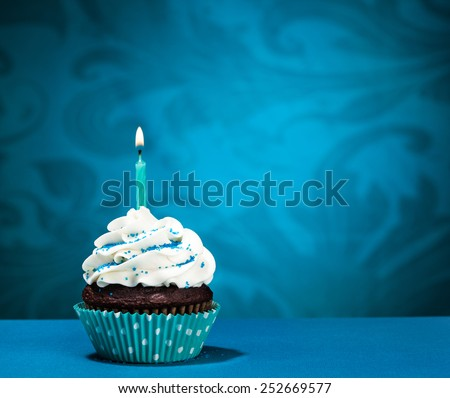 Chocolate Cupcake with  icing and lit birthday candle over a blue background