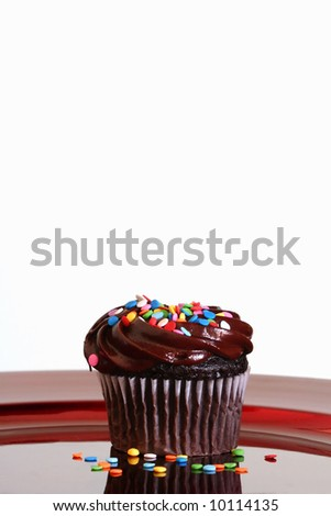 Chocolate Cupcake with Sprinkles on Red Plate with Copy Space