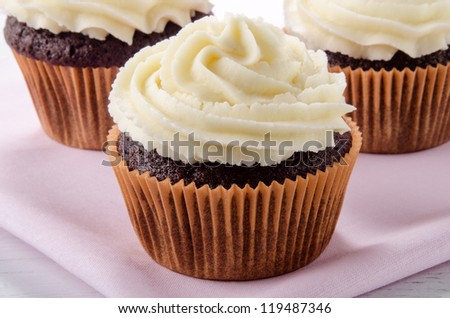 chocolate cupcake with vanilla butter cream on a pink napkin
