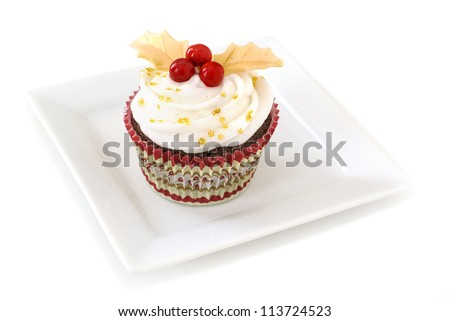 Chocolate cupcake with vanilla frosting decorated Holly made of with gold fondant leaves and red candy. - stock photo
