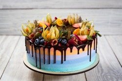 Chocolate cupcakes with colored layers decorated  by fruit, berries and candy as birthday concept