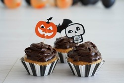 Chocolate cupcakes with halloween decoration and balloons in the background