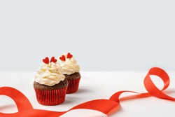 Chocolate cupcakes with red hearts and with red ribbon. Greeting for Valentine's Day
