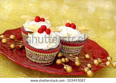 Chocolate cupcakes with vanilla icing decorated with gold colored fondant leaves and red candy.