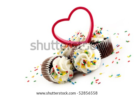 Chocolate cupcakes with white frosting and colored sprinkles with a plastic red heart copy space