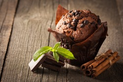 chocolate dark cooked muffin with mint on a wooden table with cinnamon, anise, chocolate.