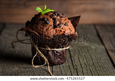 chocolate dark muffin with a leaf of mint on a wooden table with cinnamon, anise, chocolate #475265527