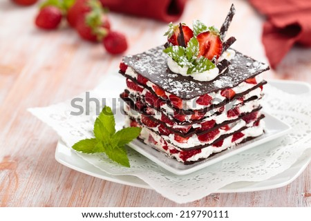 Chocolate dessert with strawberries, whipped cream and mint.