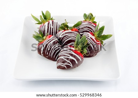 Chocolate dipped strawberries with white chocolate drizzle on a small serving plate.