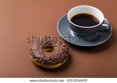 Chocolate donut and cup of black coffee on brown background. Monochromatic concept. #1051856600