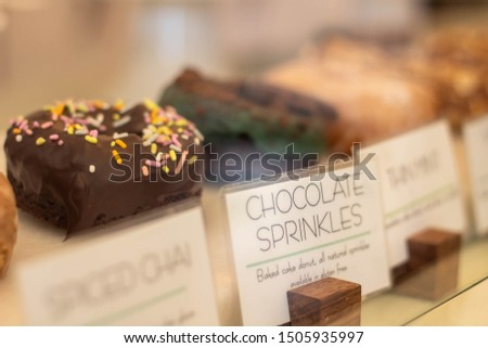 Chocolate donut with sprinkles in bakery display case with other tempting doughnuts, focus on chocolate doughnut  and description tag label,
