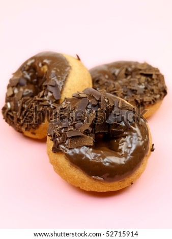 Chocolate donuts isolated against a pink background