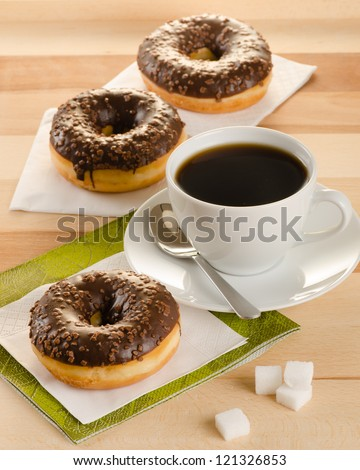 Chocolate donuts with coffee and sugar on the wooden table