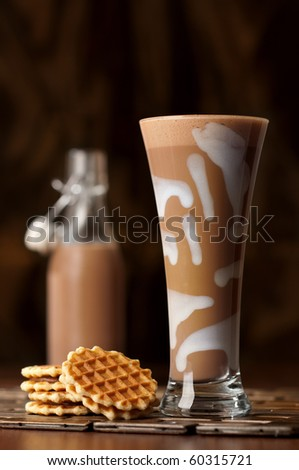 Chocolate drink in decorated glass with wafer biscuits on rich background