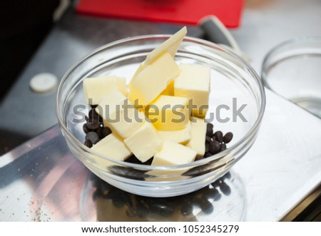 Chocolate drops and butter in a glass bowl. #1052345279