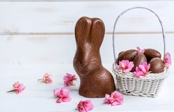 Chocolate Easter Bunny,Chocolate Eggs and Pink Flowers on a White Wooden Background .Easter Greeting Card