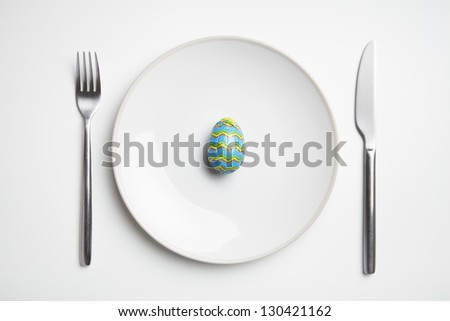 Chocolate easter egg on plate with knife and fork