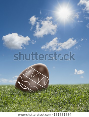 chocolate easter egg with decoration on spring landscape