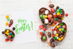 Chocolate easter eggs and colorful sweets on wooden background greeting card. Top view. Flat lay