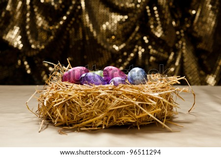Chocolate Easter eggs in a natural straw nest in front of a beautiful golden background