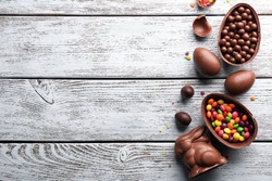 Chocolate Easter eggs, rabbit and sweets on light wooden background