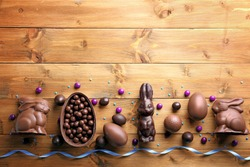 Chocolate Easter eggs, rabbits and sweets on wooden background