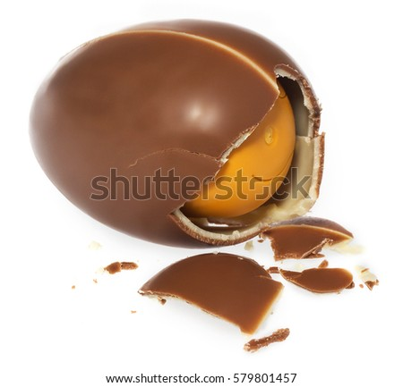 Chocolate egg surprise. Gift egg broken on the side, pieces of crushed chocolate. The composition on a white background with slight shadow. #579801457
