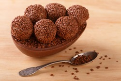 Chocolate egg with filling of brigadeiro for Easter on wooden background. Selective focus