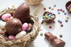 Chocolate eggs and easter almonds on bird nest, chocolate bunny and sweets on white wooden table