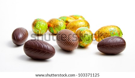 Chocolate eggs and eggs in foil isolated on white background
