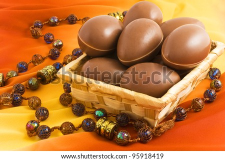 chocolate eggs in a wicker basket on a background of yellow-brown silk, decorated with large colored glass beads in oriental style