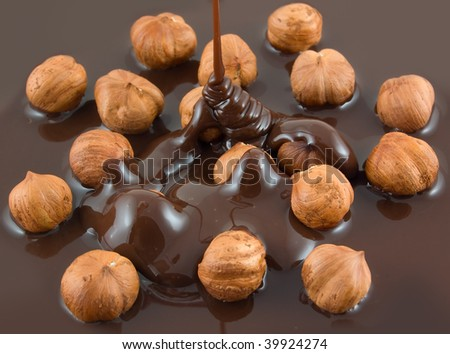 Chocolate flows on nuts. Tasty look - abstract food background