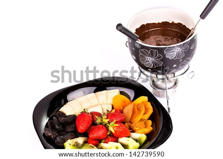 Chocolate fondue with fruits isolated on white background