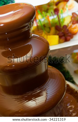 Chocolate fountain against fruit