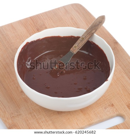 Chocolate Frosting in a White bowl with a Mixing Spatula, all on a bamboo cutting board.  It's mixed and ready for spreading on a cake, cupcakes or any other dessert or confectionery.