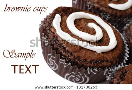 Chocolate fudge brownies baked in fun paper wrappers with swirl of  vanilla icing to match design of cups.  Macro on white background with copy space.