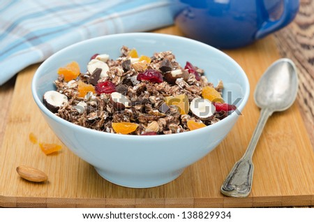 Chocolate granola with nuts and dried fruit on a wooden board horizontal