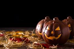 Chocolate Halloween pumpkins on wooden table. Copyspace