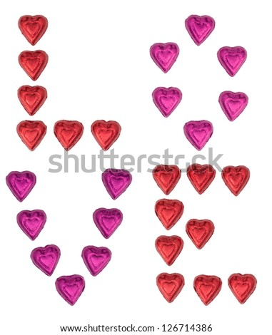 Chocolate heart candy wrapped in red and pink foil arrange to spell out LOVE isolated on white