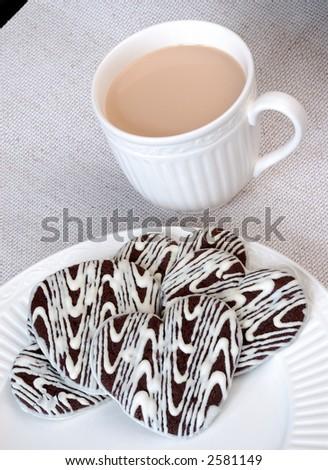 Chocolate Heart Cookies and Vanilla Cappuccino - White and dark chocolate heart shaped cookies on a white plate and a cup of vanilla cappucino.