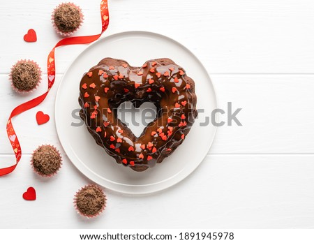 Chocolate heart shaped bundt cake covered by chocolate glaze and red sprinkles and chocolate truffles. Saint Valentine's day dessert. Festive food. Top view. Copy space. White wooden background.