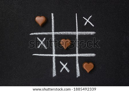 Chocolate hearts and grid of tic-tac-toe on black grainy cardboard. Love game concept. Flat lay Foto stock ©