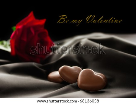 Chocolate hearts on fabric with red rose. Available space for your text.