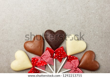 Chocolate hearts with bows. Background with sweets for Valentines Day.
