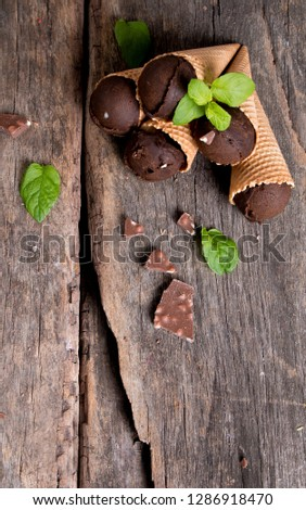Chocolate ice cream scoops in sweet cone on wooden table.