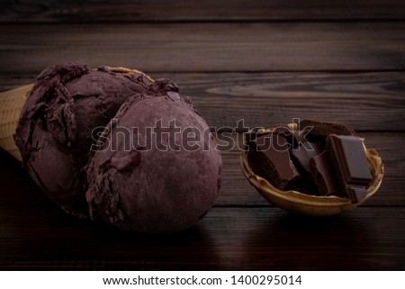 chocolate ice cream scoops in waffle cones and chocolate pieces on wooden background.