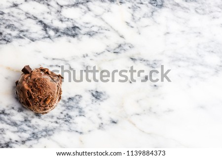 Chocolate ice cream scoops on marble background, top view