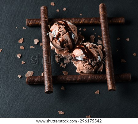 Chocolate ice cream with wafer sticks, chocolate chips and sauce on black background