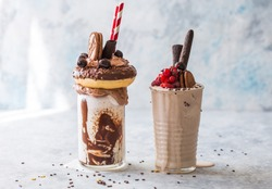 Chocolate indulgent frosting exreme milkshake with donut  and sweets. Crazy freakshake food trend. Copy space